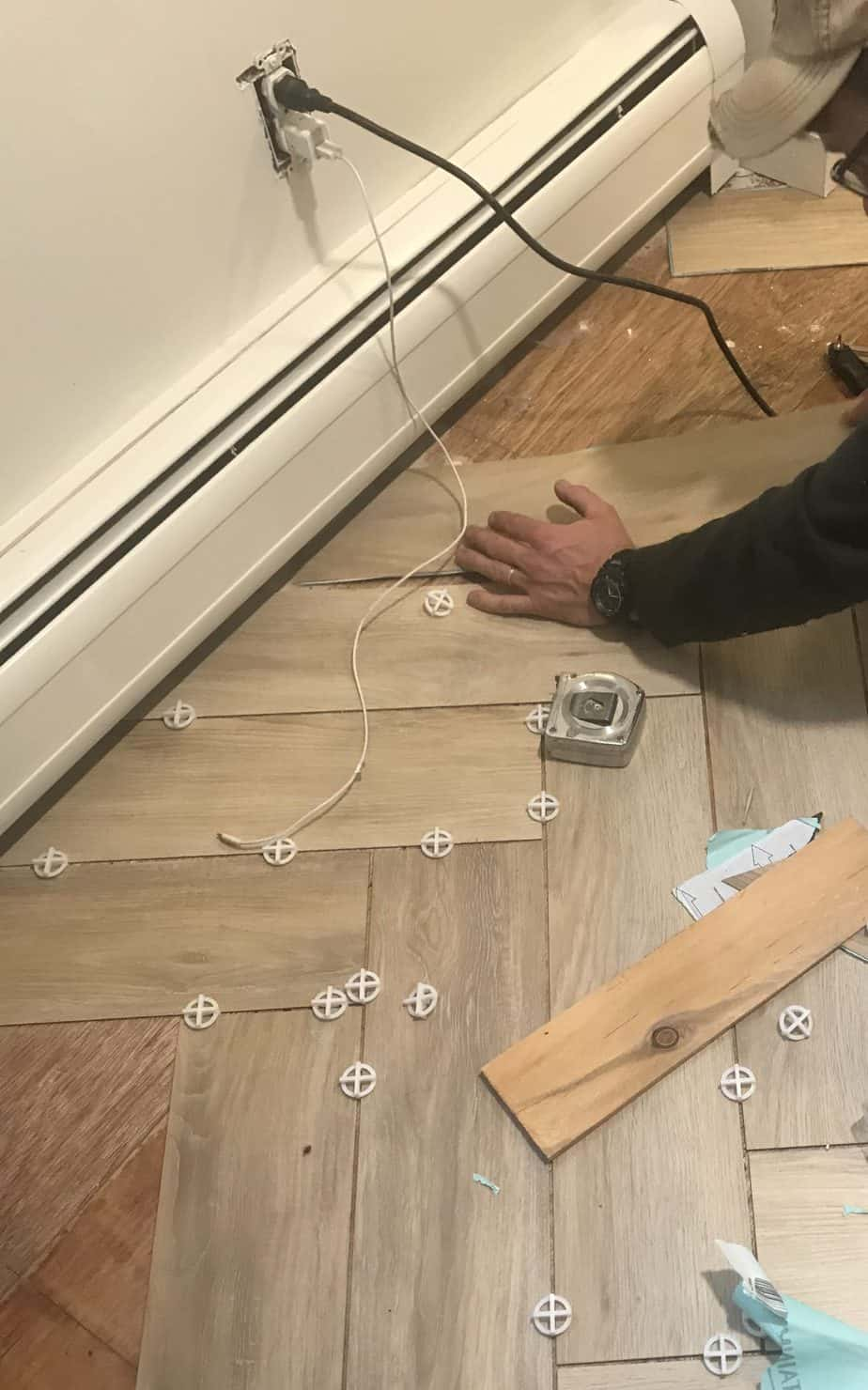 Peel and stick tile being laid in a herringbone pattern on the floor.
