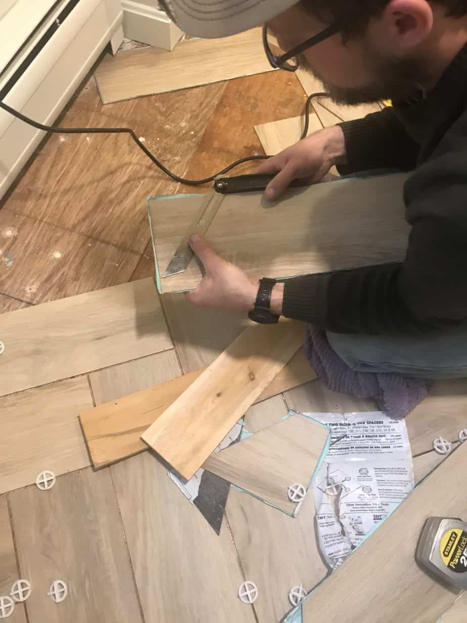 T-bevel measuring a tile and cutting it to size.