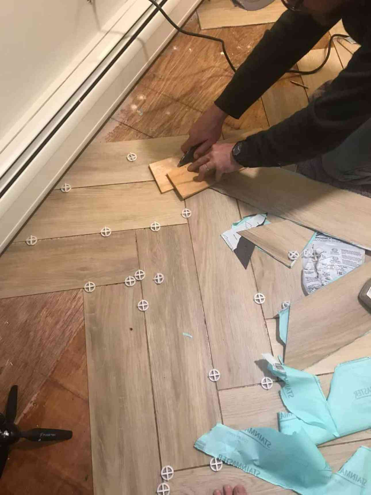 Man cutting peel and stick tile with utility knife.