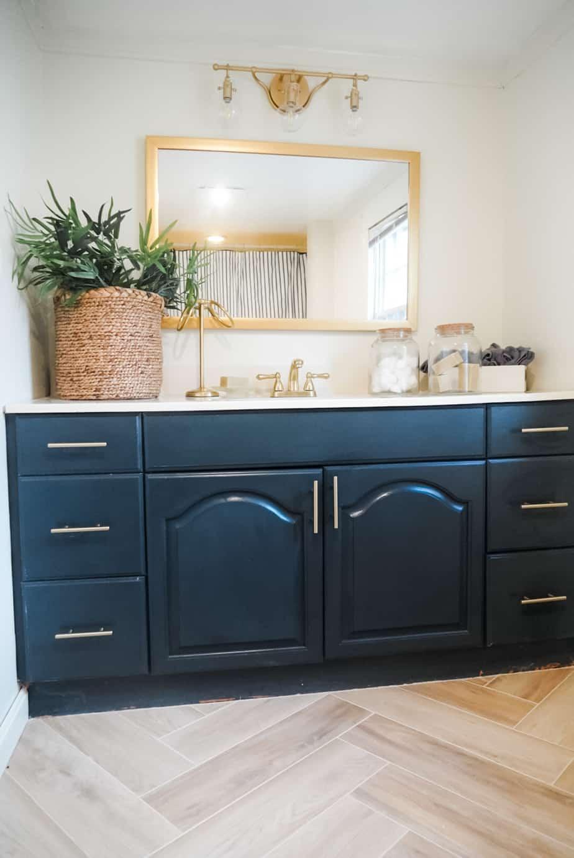 Blue bath vanity and herringbone floor.