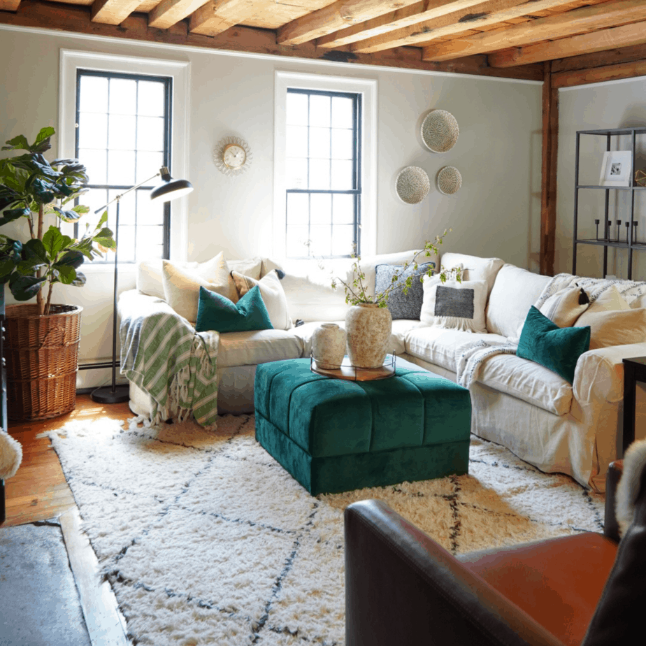 White couch, wood ceiling, and green ottoman in the living room.