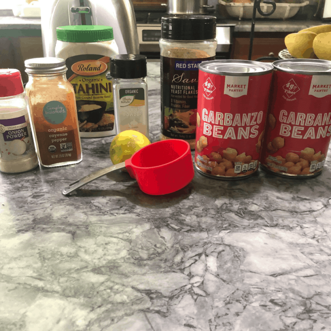 Garbanzo beans, seasonings, and a red measuring cup on the counter to make the hummus.