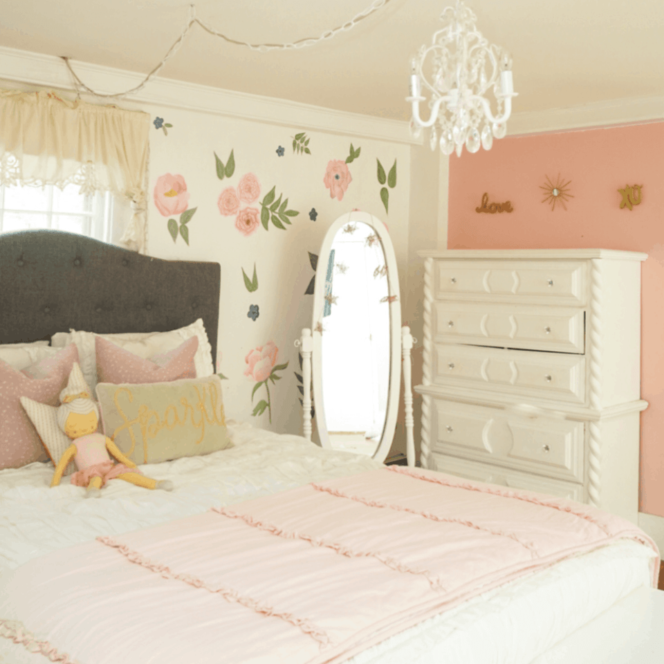 white bedding with coeval mirror and pink wall with flowers