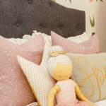 Little girl stuffed doll with pink pillows on white bedding
