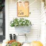 front porch decor with orange fall sign that says hello Fall