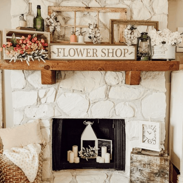 white fireplace with wooden mantel and flower shop sign.