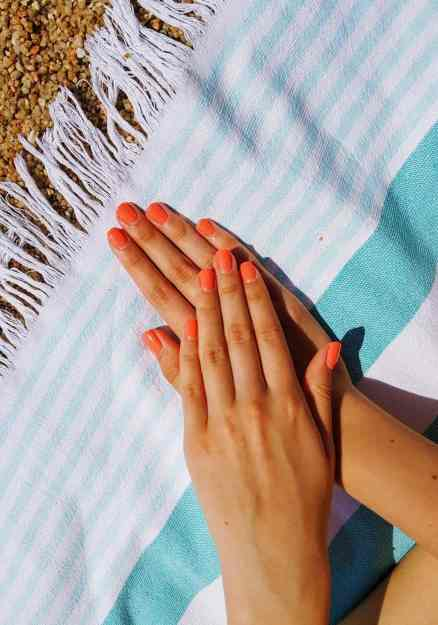 Woman two hands stacked on top of one another on top of a blue stripped towel with manicured pink nails.