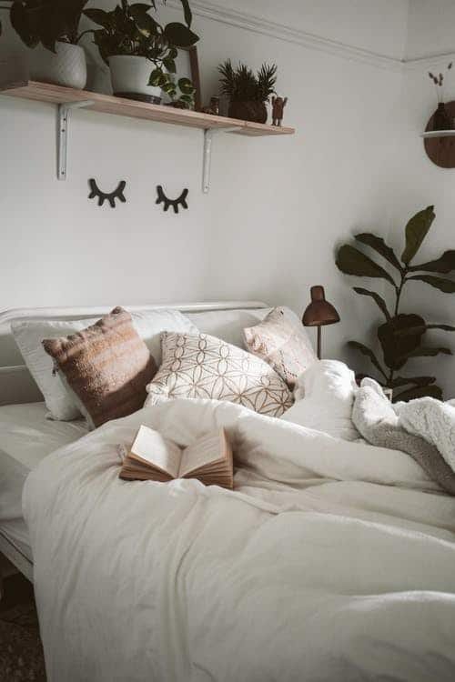 boho bedroom with pillows tossed and eyes winking on wall