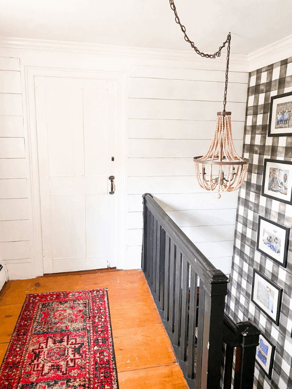 upstairs landing with wooden beaded chandelier, buffalo check wallpaper, and shiplap on wall.