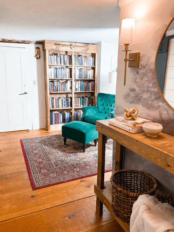 Library reading nook with an emerald green chair, antique lights, and a red boho rug. Large builtin bookcase.