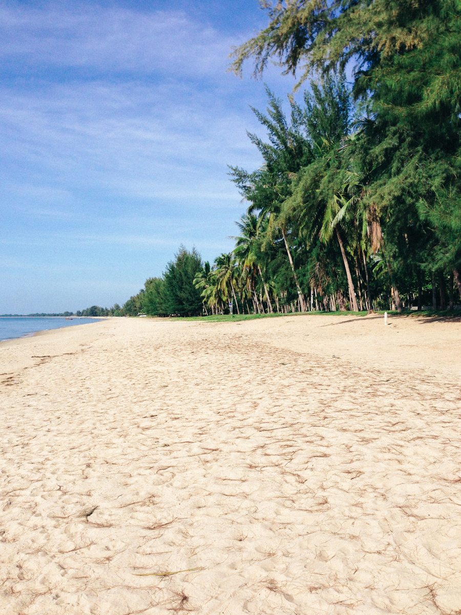 Thailand deserted beach with white sand & palm trees.