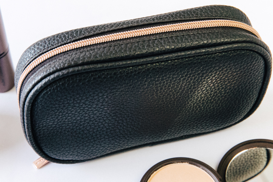 Black faux leather makeup bag with rose gold zip.