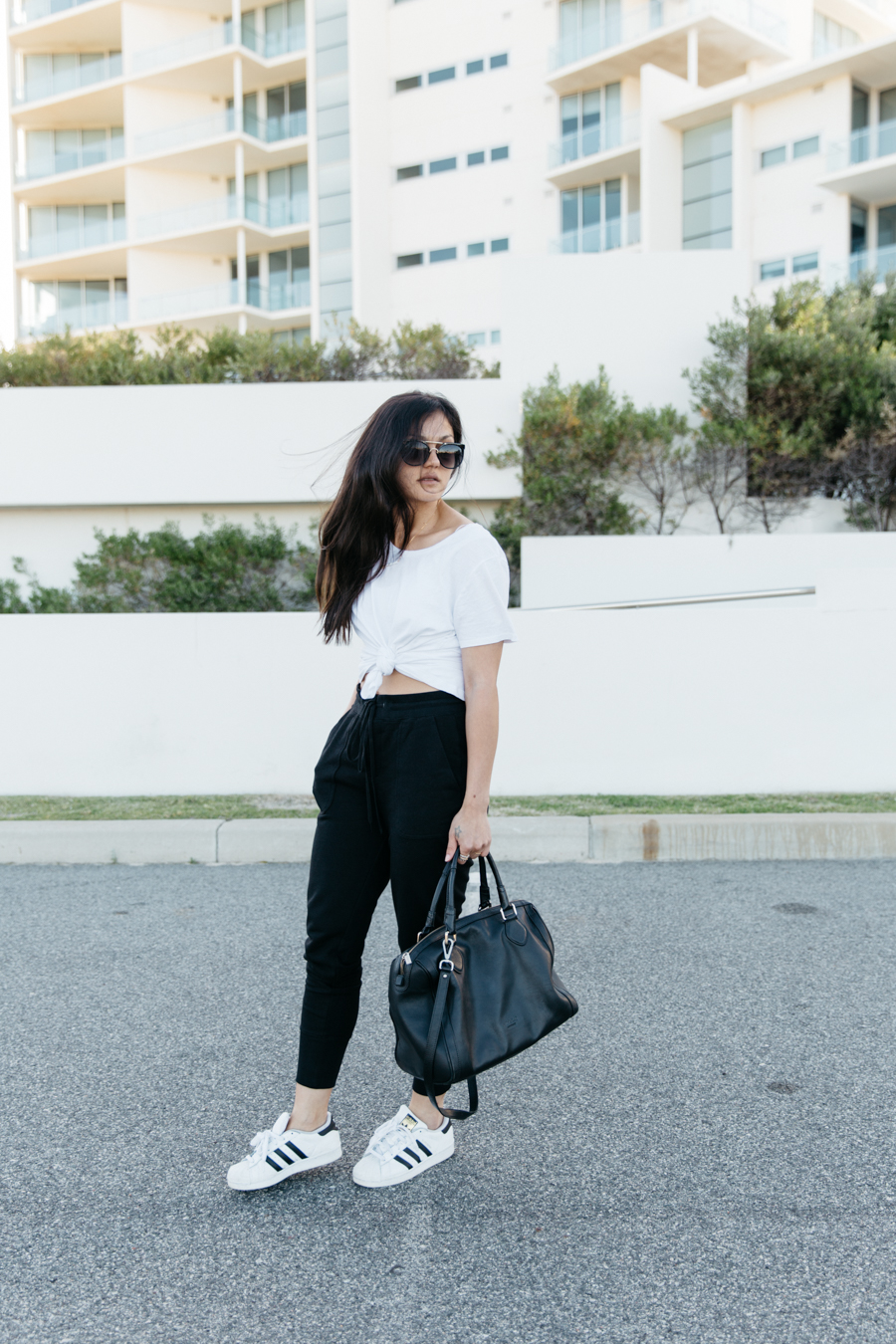 Black leather bowler bag, sweat pants outfit, white knotted tee.