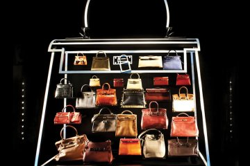 """That tradition was shaken last year when LVMH, the world's largest agglomeration of luxury marques (including Louis Vuitton), acquired a 22 per cent stake in Hermès. To secure Hermès from LVMH, 50 relations from three branches of the family recently met to establish a watertight holding company that owns 51 per cent of Hermès, and which cannot be sold for 20 years. """"Although we're confident,"""" Pierre-Alexis says, """"we will remain paranoid until the end. It was really a Nietzschean moment, it didn't destroy us, so it made us stronger. When I pass this company on to the seventh generation, then I will believe I've done my job."""" """"No,' Pierre-Alexis says baldly. 'I don't. It's not my bag."""" A few days later, I visit an Hermès facility on the outskirts of Paris. Once my passport is politely confiscated, and I am firmly admonished against photography, the experience proves cheery. The vision of Hermès at the Leather Forever exhibition did not include the snaps of David Beckham or Daphne Guinness (toting an Hermès) that are Blu-Tacked to Parisian workers' desks, or the laughter-punctured murmur of chatter, machine-whirr and banging (during 'perlage', the attachment of hardware to bags) that fills the room. The craftsmen and women I meet (all quite young) appear both genuinely charming and charmed by their jobs. They say the Plume – the company's oldest bag design – is the most difficult to make, and that the average time it takes to make a bag is two and a half weeks. A recently hired 17-year-old named Dimitri, wearing piercings and jeans, has just finished his first Kelly, coloured a glowing light blue, and made inside out to reduce the appearance of stitching on the exterior. In front of us, with infinite slowness and the help of a tiny iron to reduce stress to its calfskin, he turns the bag outside in again – and beams like a new father when the delivery is flawlessly complete. Another worker, a cool, slightly older chap named Julien Serange, says, """"We don't feel like mach"""