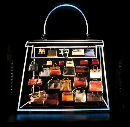 """That tradAn installation of iconic Hermès bags in the brand's Shanghai flagship storeition was shaken last year when LVMH, the world's largest agglomeration of luxury marques (including Louis Vuitton), acquired a 22 per cent stake in Hermès. To secure Hermès from LVMH, 50 relations from three branches of the family recently met to establish a watertight holding company that owns 51 per cent of Hermès, and which cannot be sold for 20 years. """"Although we're confident,"""" Pierre-Alexis says, """"we will remain paranoid until the end. It was really a Nietzschean moment, it didn't destroy us, so it made us stronger. When I pass this company on to the seventh generation, then I will believe I've done my job."""" """"No,' Pierre-Alexis says baldly. 'I don't. It's not my bag."""" A few days later, I visit an Hermès facility on the outskirts of Paris. Once my passport is politely confiscated, and I am firmly admonished against photography, the experience proves cheery. The vision of Hermès at the Leather Forever exhibition did not include the snaps of David Beckham or Daphne Guinness (toting an Hermès) that are Blu-Tacked to Parisian workers' desks, or the laughter-punctured murmur of chatter, machine-whirr and banging (during 'perlage', the attachment of hardware to bags) that fills the room. The craftsmen and women I meet (all quite young) appear both genuinely charming and charmed by their jobs. They say the Plume – the company's oldest bag design – is the most difficult to make, and that the average time it takes to make a bag is two and a half weeks. A recently hired 17-year-old named Dimitri, wearing piercings and jeans, has just finished his first Kelly, coloured a glowing light blue, and made inside out to reduce the appearance of stitching on the exterior. In front of us, with infinite slowness and the help of a tiny iron to reduce stress to its calfskin, he turns the bag outside in again – and beams like a new father when the delivery is flawlessly complete. Another worker, a co"""
