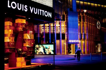 A LVMH Moet Hennessy Louis Vuitton store and a Gucci Group NV store are illuminated at night in Macau, China