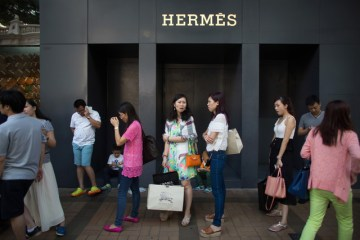 Customers wait in line to enter an Hermes store in Hong Kong