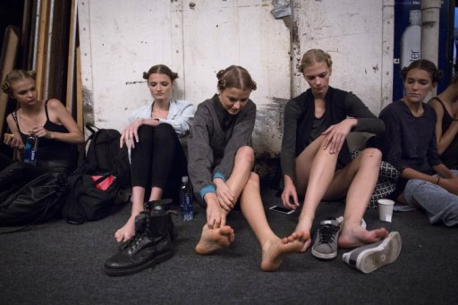 Models relaxing backstage, their feet in agony by the looks of it.