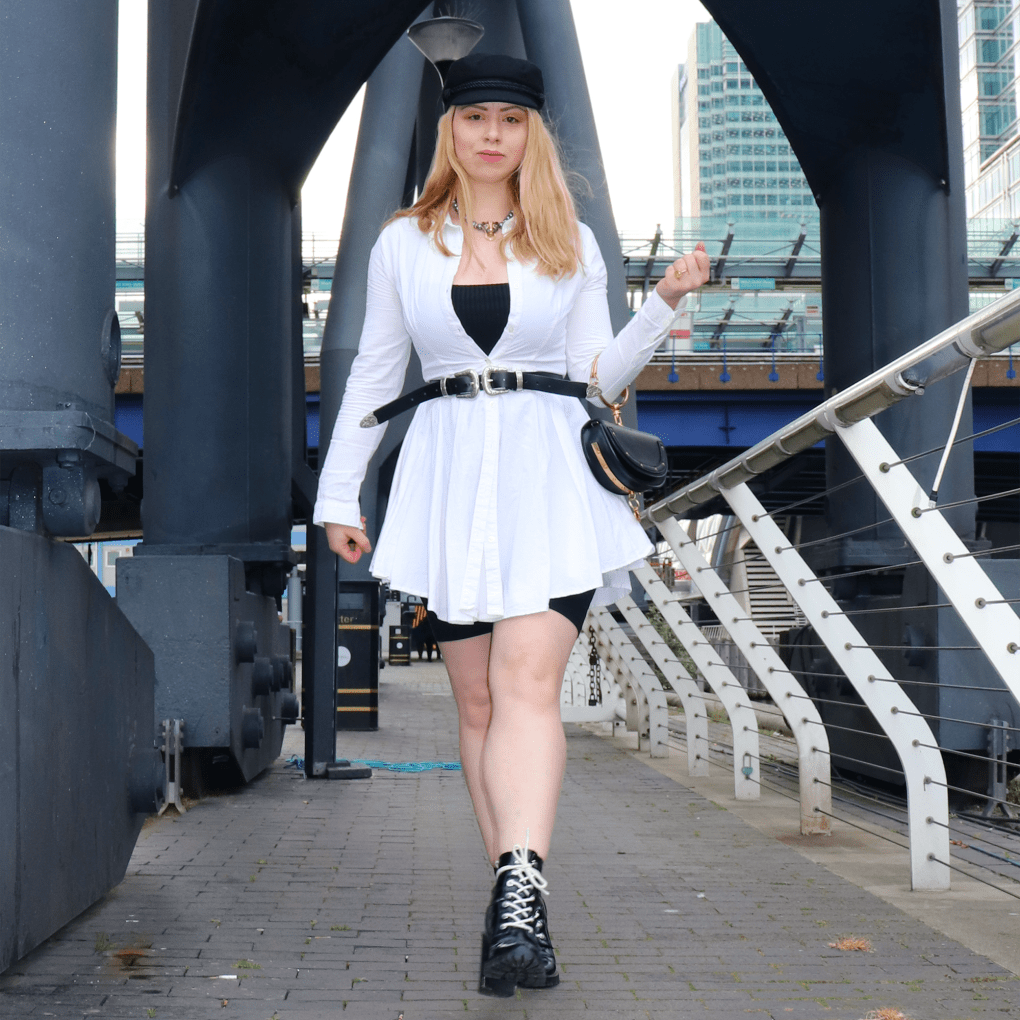 blonde woman wearing white shirt dress, black boots and carrying a Chloe handbag in a cityscape by docks