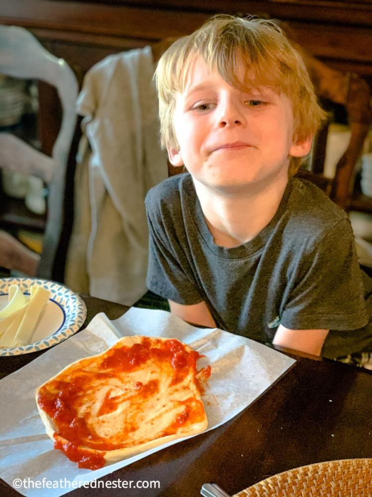 photo of child making a pizza