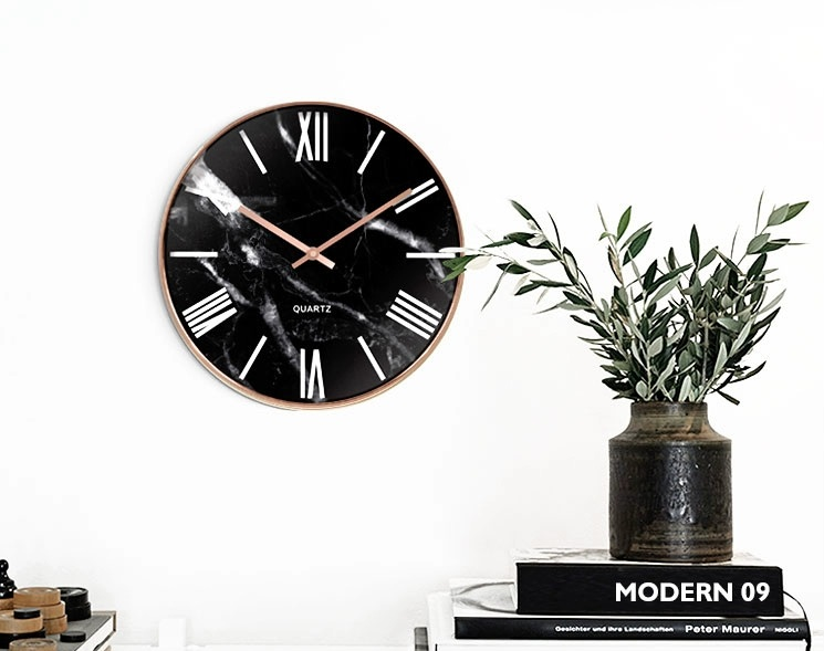 Marble clock on the wall with plotted plant and books as decorations