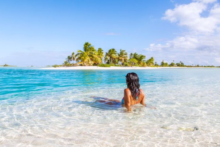 Girl relaxing on a beach in a clear blue water looking towards a small island with palm trees