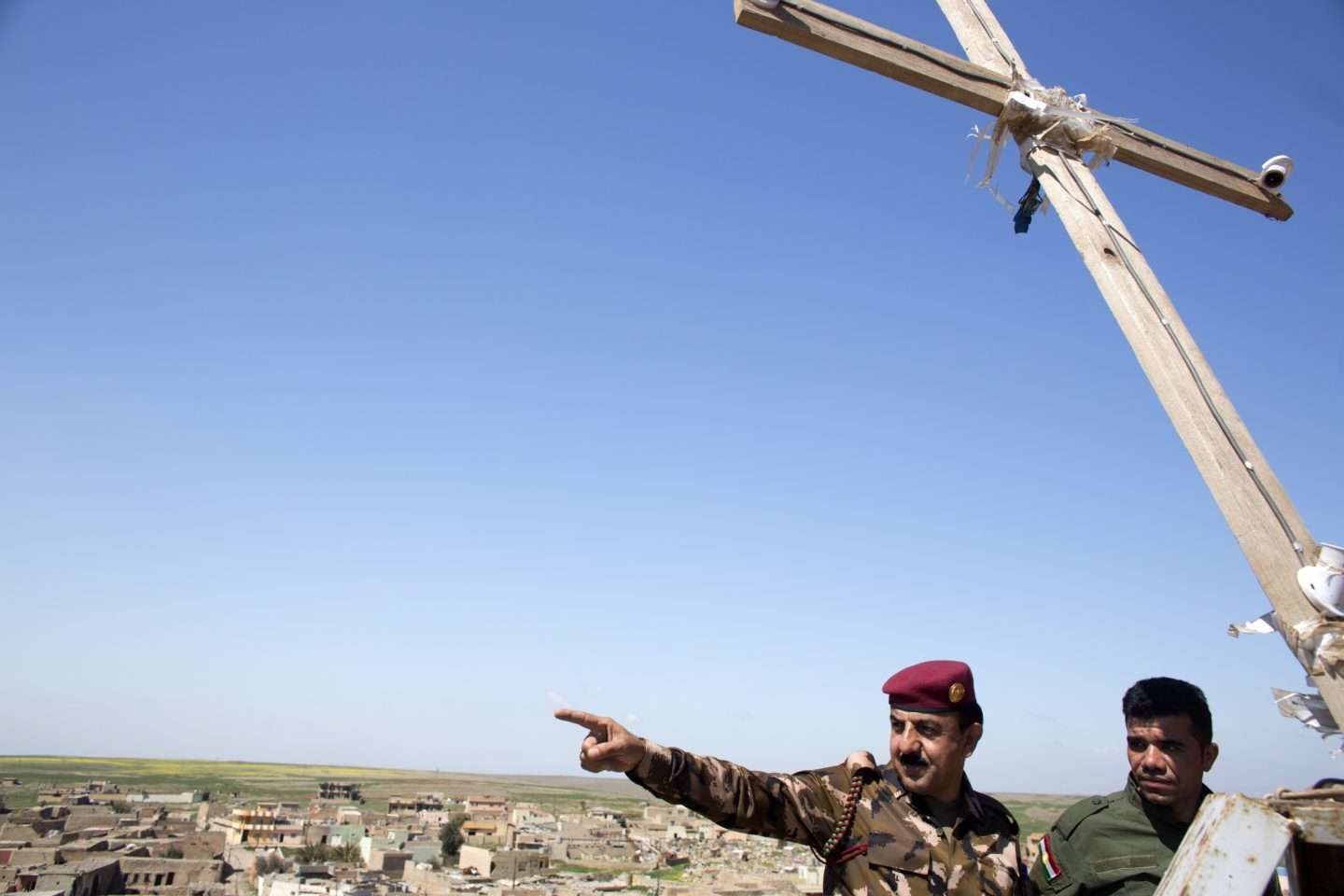 The Peshmerga's Major Jaffer points to a cemetery about half a mile away