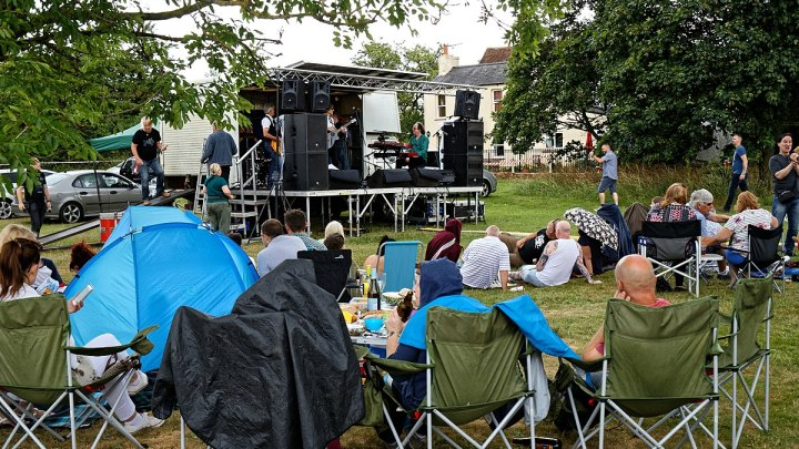Spectators watching a covers band (Archive) performing on a temporary mobile outdoor stage at the Hatfield Heath Festival 2017, on Hatfield Heath village green, Essex, England.