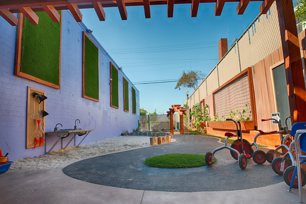 After. View looking South. The tricycle track is the spine that runs through the yard. Vertical planters help to soften the walls, providing planting areas, and maximizing the ground level for play. image: Alex Calegari