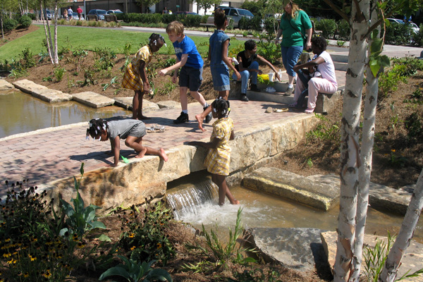 Birmingham's Railroad Park has catalyzed development downtown and significantly reduced local flooding thanks to a one-acre lake that doubles as a detention basin, a recreated stream system, and other green infrastructure. image: Tom Leader Studio