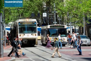 A busy street in Portland, Oregon with pedestrians, buses, and trams