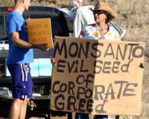"""A Monsanto protester holds up a sign reading """"Monsanto: Evil Seed of Corporate Greed."""""""