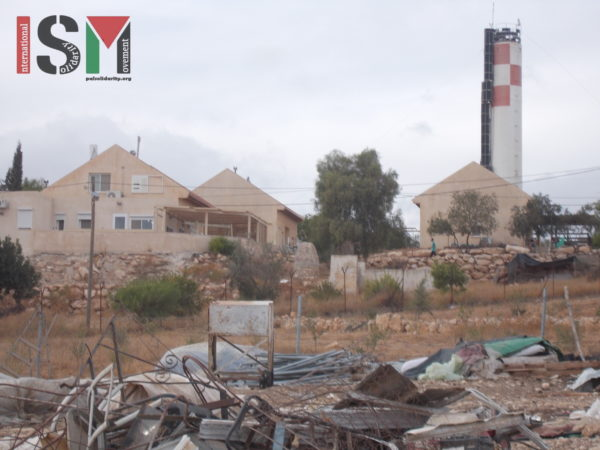 Rubble from the demolition, with the luxurious houses in the illegal settlement in the background