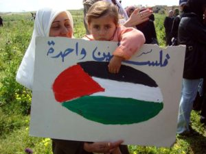 By ISM Palestine - originally posted to Flickr as Palestinian child holds a sign on Land Day, CC BY-SA 2.0, Via Wikimedia Commons