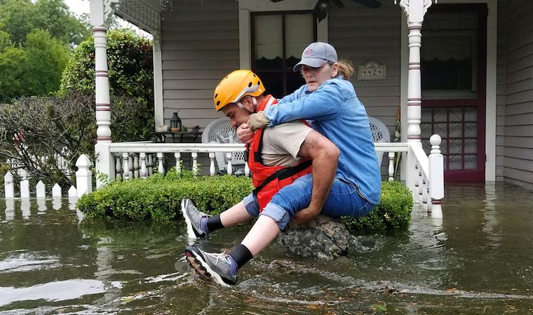 A Texas National Guardsman carries a residents from her home during flooding caused by Hurricane Harvey