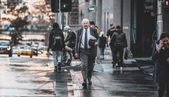 man walking across Melbourne street