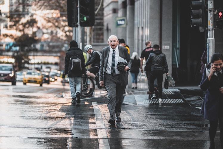 man walking across Melbourne street
