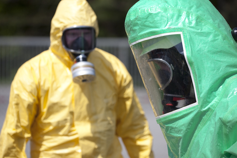 Two men in protective gear cleaning up after chemical accident or radiation accident. The inflatable gear to the right protects against contamination with radioactive particles, against Alpha radiation and partially against Beta radiation. Focus on the right green person.