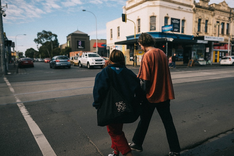 housing first, man and woman walking across Melbourne street