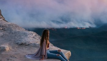 woman looking at blue mountains fires