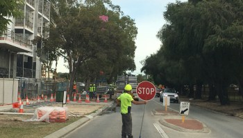 PERTH, WA - APR 23 2021:Builder holding a stop sign outside building site.Construction industry accounts for more than 10% of global GDP and employs around 7% of the global workforce over 273m people.