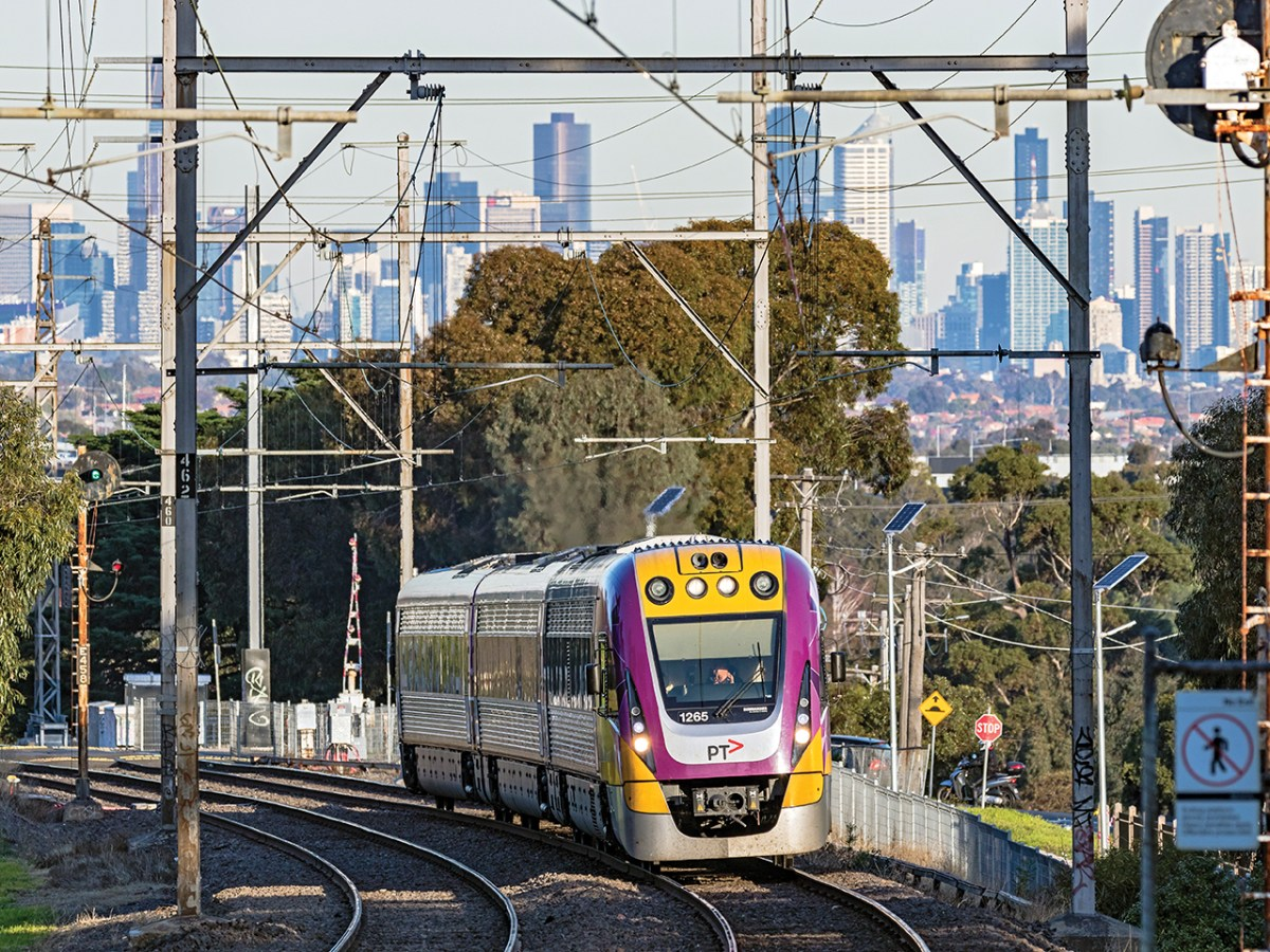 Melbourne, Australia – June 16, 2017: Modern Bombardier Velocity 3-car regional train with PTV logo and latest colours climbs uphill on a Seymour service with the downtown city centre in the background. Close-up view.