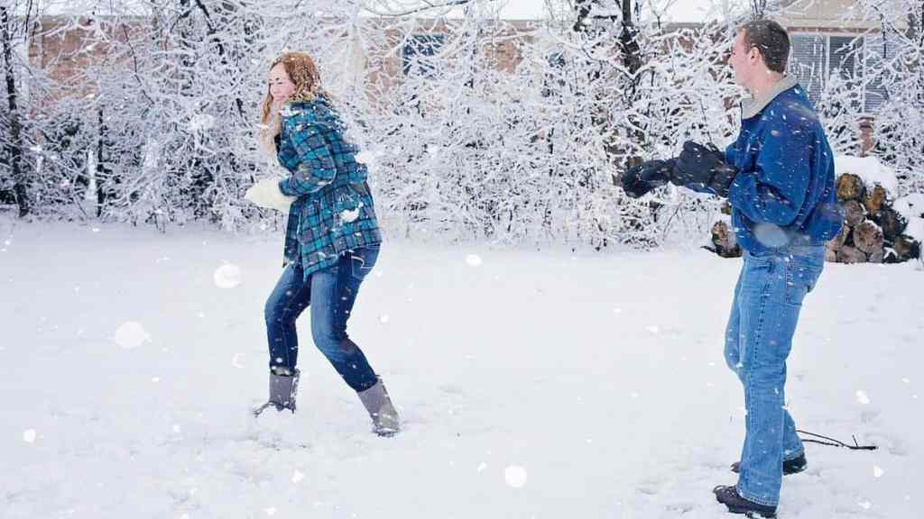 millennials in a snow ball fight after paying down debt