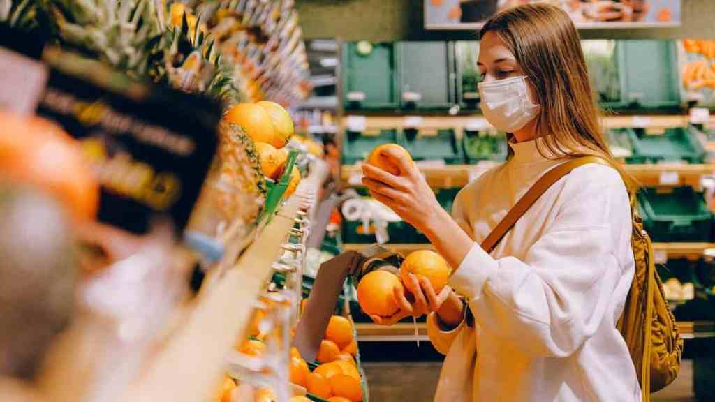 a millennial grocery shopping for oranges while on a budget to save money on food