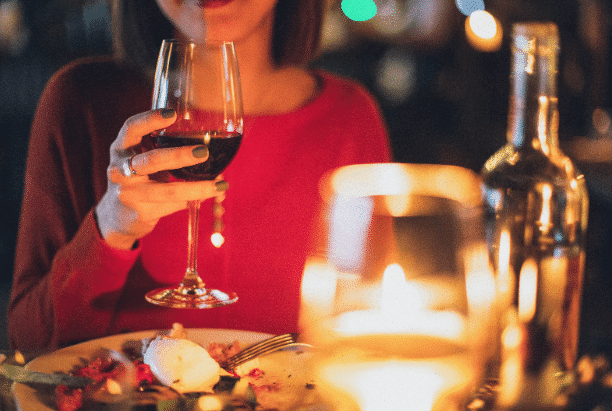 A lady holding a glass of wine on a date