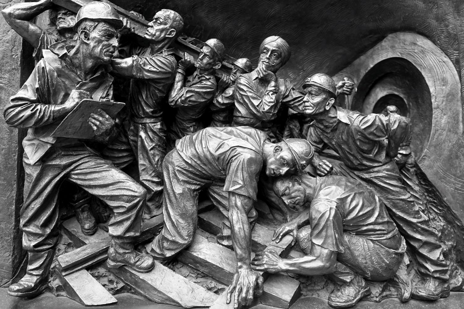 Scuplture of miners, hard at work. Cramped. Struggling.