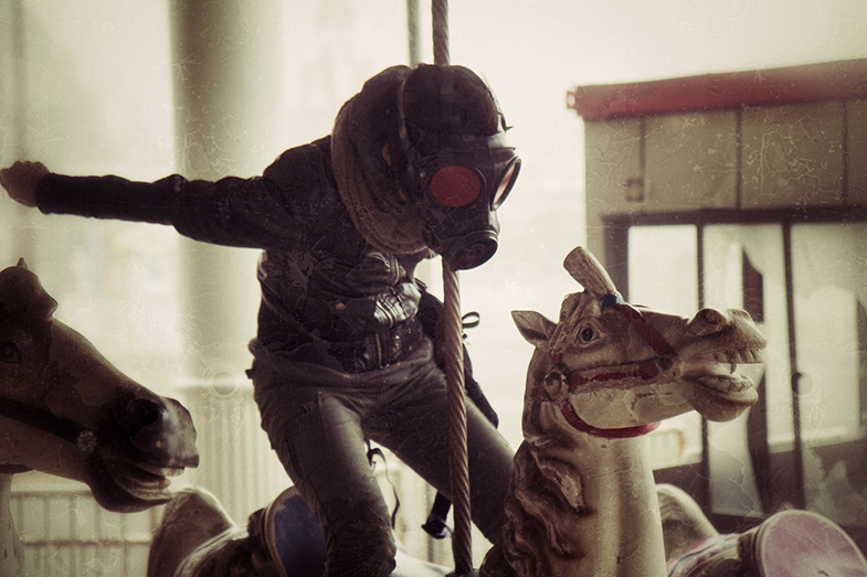 A gas-masked youth in leathers rides a crazed merry-go-round horse in a post-apocalyptic fun-fair.