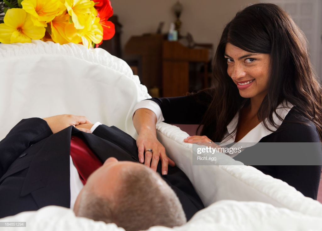 Writing prompt: A woman standing by an open-casket, touching the corpse within. She catches our eye...and smiles slyly.
