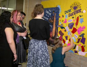 A group of women stand in front of a piece of art. Some are reading and others are interacting with it by writing on it. They are all wearing nice dresses.