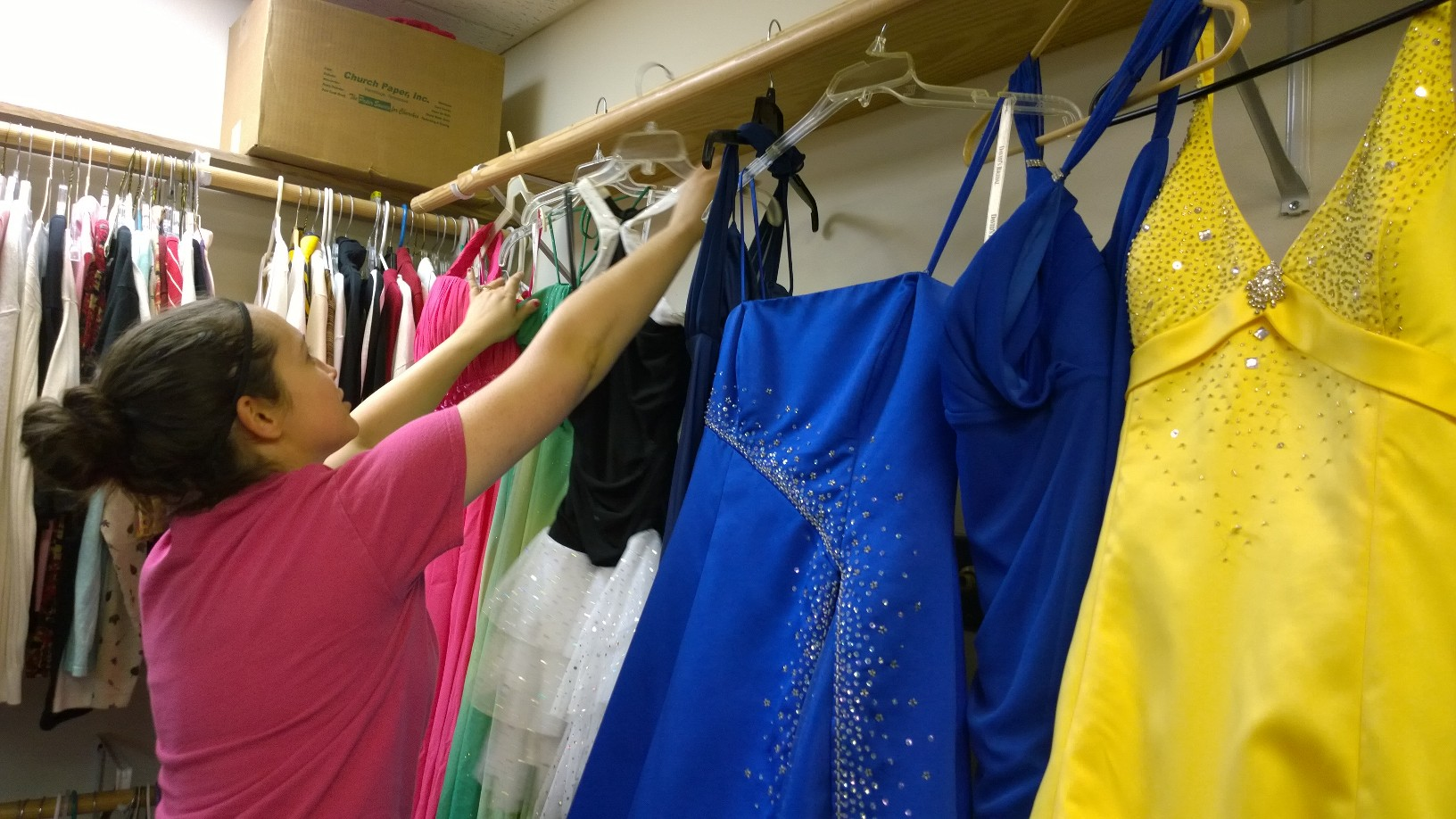 Mandi Daniels, a prom closet volunteer, helps hang newly donated dresses to be steamed and hung in the prom closet to await the next prom. || JESSIE HORTON photo